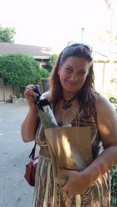 Jennifer as herself, rather than as comedian Jen Eros, on a trip to Watts Winery tasting room, with a bottle of their Old Vine Zinfindal.  She will be back, September 28, with Inner City Productions jazz and art event, working with the art display.